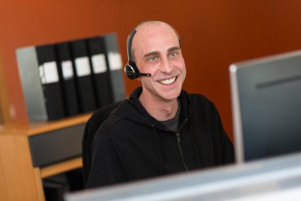 Anställd hos Fastighetssnabben pratar i ett headset.